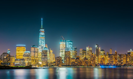 Long exposure of New York City Skyline with dark blue sky, bright yellow city lights and reflections in the river