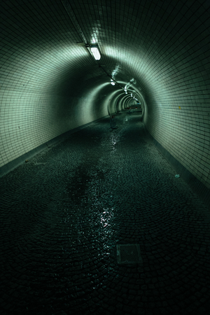 Dark road in a dirty grunge tunnel with wet road and bluegreen ceiling light