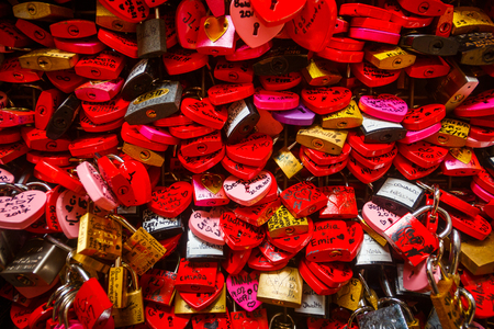 Wall full of red and pink love locks shaped as hearts and classical locks with writings on each lock, in Verona, Romeo & Julie Wall