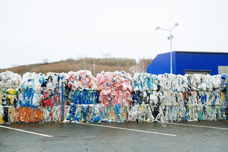 Packs and Stocks of Wrapped Scrap Plastic Dedicated for Eco Recycling in front of a Recycling Factory