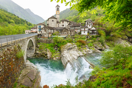 View on the Lavertezzo village, famous tourist destination - An old Swiss village with double arch stone bridge at Ponte dei Salti with waterfall, Lavertezzo, Verzascatal, Canton Tessin