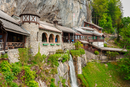 St. Beatus Cave and waterfalls above Thunersee, Sundlauenen, Switzerland. Falls are running down the mountain with a green grass and long exposure of waterfalls