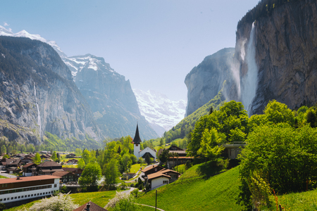 Scenic view on Lauterbrunnen historic village with church, gigantic mountains, waterfall and green grass in Bern canton, Switzerland Stock Photo