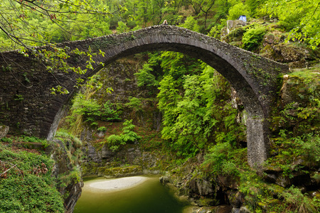 Side View on the Ponte Romano Intragna Bridge hiding in the valley with beautiful river covered with trees, close to Verzasca village. It is the oldest bridge in Switzerland.