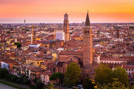 Aerial view of Verona city night cityscape and Church Santa Anastasia, with  Adige river , located in Veneto, Italy, viewed from Castel Saint Pietro with glowing yelloworange sunset sky