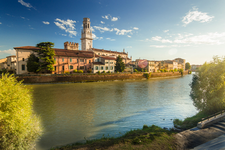 Verona cityscape during late sunset with Adige river and Church Complesso della Cattedrale-Duomo, viewed from the opposite side of river. Verona is located in Veneto, Italy, Stock Photo