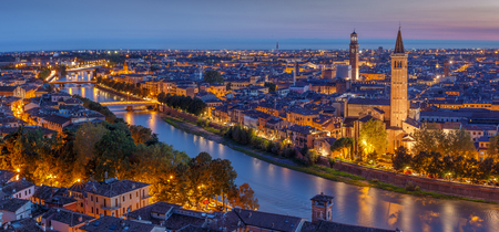 Aerial view of Verona city night cityscape and church Santa Anastasia, with  Adige river , located in Veneto, Italy, viewed from Castel Saint Pietro with blue sky and glowing yellow city lights