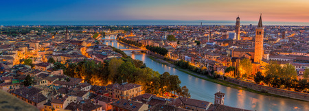 Aerial view of Verona citycityscape day to night transition and church Santa Anastasia, with  Adige river, located in Veneto, Italy, viewed from Castel Saint Pietro with blue sky and glowing yellow city lights Stock Photo