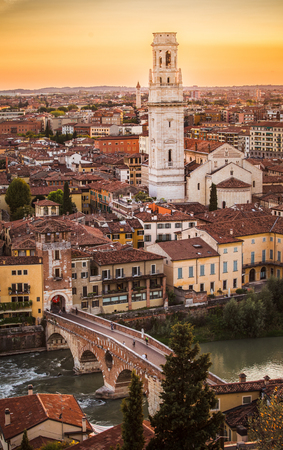 Aerial view of Verona city sunset cityscape, with  Adige river and Complesso della Cattedrale-Duomo , located in Veneto, Italy, viewed from Castel Saint Pietro with yellow sunset sky