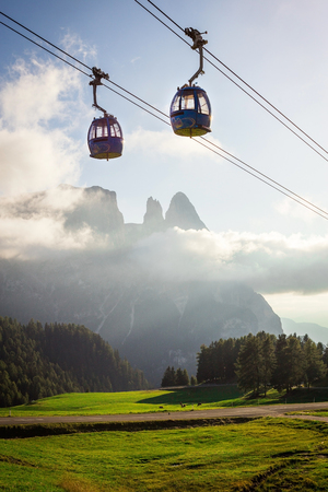 Aerial Tram Cable Car going up, during sunset, with beautiful high mountains in the background in Alpe di Siusi, Dolomites, Italy