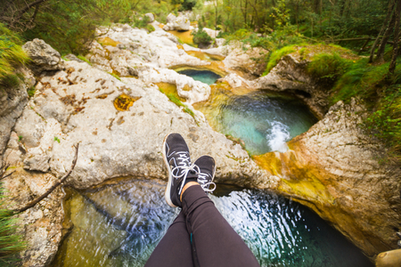 Relaxing with crossed legs and sitting on a bridge above Cadini of Brenton, Sospirolo, Italy with azure clear water and multiple waterfalls along the way down Editorial