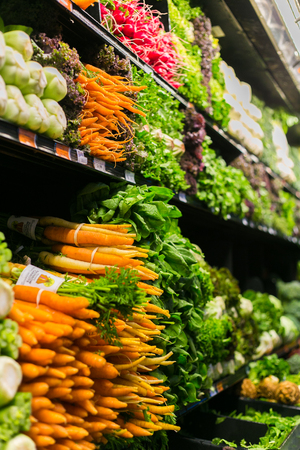 Stacks of fresh vegetable in a grocery  like carrot, salad, onion, and mushrooms in a grocery shop