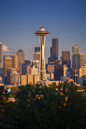 View on Seattle cityscape with Space Needle in front of skyscrapers, during early sunset with sunt hitting the buildings