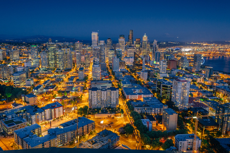 Downtown Seattle cityscape panorama with modern skyscrapers and glowing yellow city lights  beautiful blue sky, viewed from Seattle Space Needle