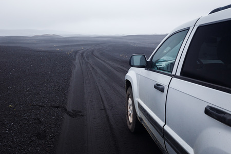 Detail of a black offroad tire on a offroad truck vehicle, built for dirty rides, on a dark ash road in Iceland Stock Photo