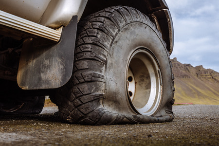Damaged flat offroad tire on a road Stock Photo