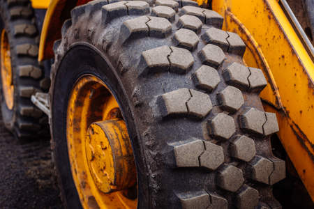Detail on tire track pattern on a yellow heavy duty digger excavator on a dark soil Stock Photo