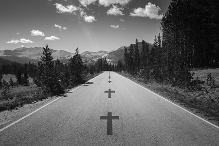 Cross, symbol of death as a line crossing on an empty concrete asphalt road close to a deadly turn in the middle of mountains in California. Stock Photo
