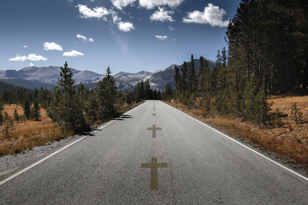 Cross, symbol of death as a line crossing on an empty concrete asphalt road close to a deadly turn in the middle of mountains in California.