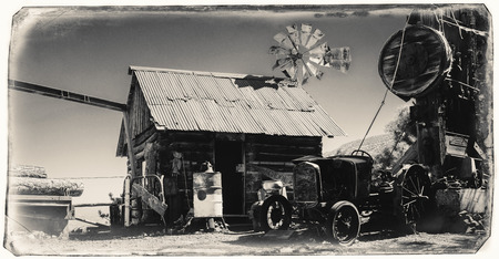 Black and White Sepia Vintage Photo of Jerome Gold King Mine & Ghost Town with old western building, windmill and an old car standing nearby 新聞圖片