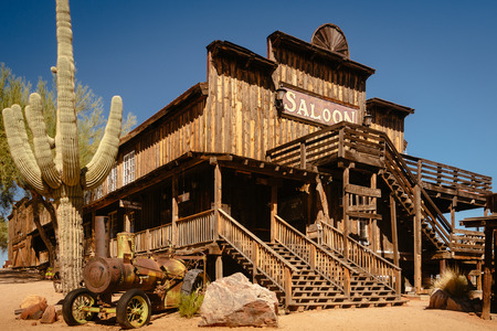 Old Wild  Western Wooden Saloon in Goldfield Gold Mine Ghost Town in Youngsberg, Arizona, USA surrounded by cactuses