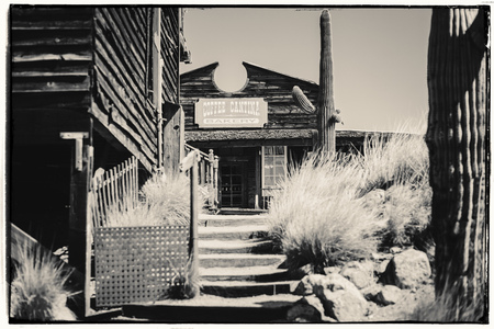 Black and White Sepia Vintage Photo of Old Western Wooden Buildings in Goldfield Gold Mine Ghost Town in Youngsberg, Arizona, USA surrounded by cactuses