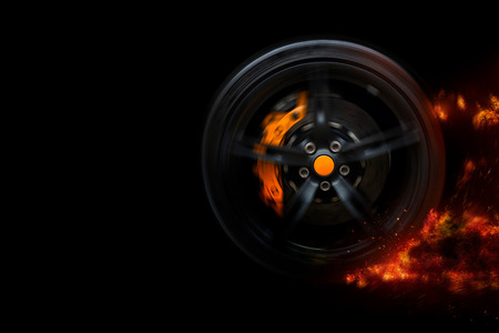 Isolated generic sport car wheel with yellow breaks drifting blazing flames of fire, smoking on a black background