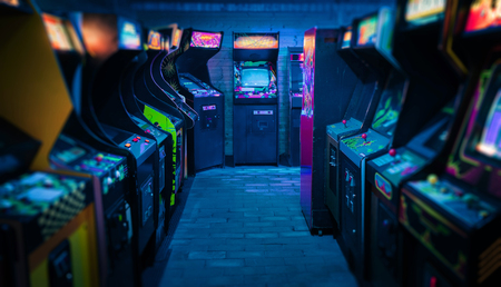 Old Vintage Arcade Video Games in an empty dark gaming room with blue light with glowing displays and beautiful retro design 版權商用圖片