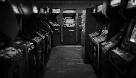 Old Vintage Arcade Video Games in an empty dark gaming room with blue light with glowing displays and beautiful retro design as a black and white photo with greyscale palette