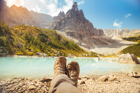 Resting with (boots) legs crossed near Lago di Sorapis, Dolomites, Italy with blue sky, azure water and high mountains in the background