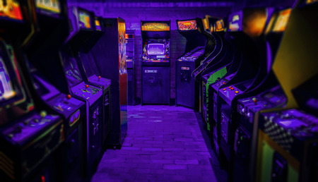 Old Vintage Arcade Video Games in an empty dark gaming room with blue light with glowing displays and beautiful retro design Stock Photo