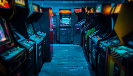 Old vintage arcade video games in an empty gaming room with dark blue light