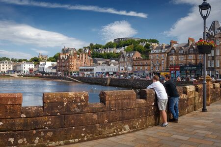July 25, 2019 - Oban, Scotland, UK: Oban City Center with tourist at the waterfront and various shops around the port, with McCaigs Tower on the top of the hill Redakční