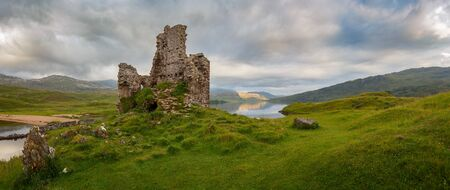 Ardvreck Castle surrounded by water and lit by sunset, located near Lairg, Scotland, UK