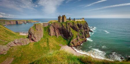 Beautiful Exterior of Dunnottar Castle with tourists in the foreground, near Stonehaven, Aberdeenshire, Scotland, UK, during sunny day