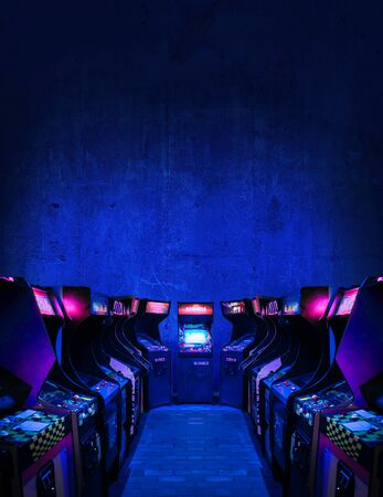 Old Unbranded Vintage Arcade Video Games in dark gaming room with bluepink light with glowing displays and concrete wall - vertical photo of retro design with free copy space for a poster or magazine Imagens