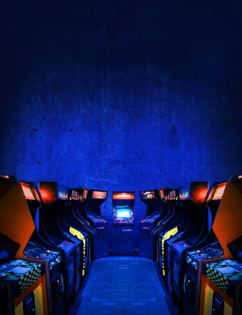 Old Unbranded Vintage Arcade Video Games in dark gaming room with blue light with glowing displays and concrete wall - vertical photo of retro design with free copy space for a poster or magazine