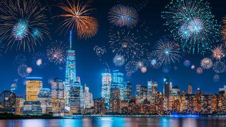 Capodanno con fuochi d'artificio colorati sullo skyline di New York a lunga esposizione con un bel cielo blu scuro, bagliore di luce arancione della città di fantascienza e riflessi nel fiume