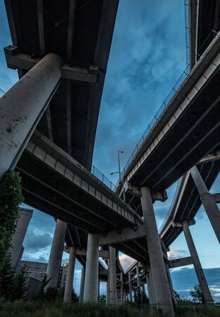 Underside of highway merging to different lanes under blue sky