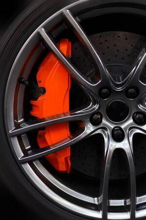 Closeup detail on a big orange sport break, on a sport tire and carbon disk breaks.