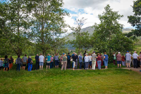 July 26, 2019 - Glenfinnan Viaduct, Scotland, UK: Plenty of tourists photographing a passing steam train at Glenfinnan Viewpoint vith view on the famous Glenfinnan Viaduct, featured in Harry Potter movie series