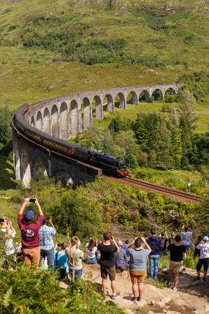 Glenfinnan Viaduct, Scotland, UK - 26 July, 2019: Crowds of tourists photographing Glenfinnan Viaduct surrounded by mountains during sunny day Editorial
