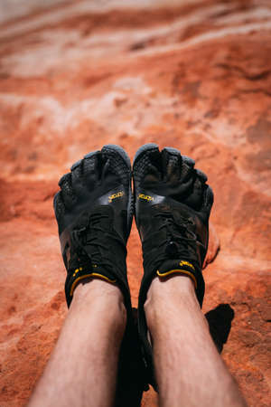 Valley of Fire, Nevada, USA - October 6, 2019: Detail on a person wearing Vibram Five Finger hiking shoes at Fire wave, Valley of Fire national park,