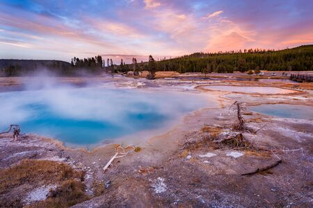 Black Diamond Pool in Biscuit basin with blue steamy water and beautiful colorful sunset. Yellowstone, Wyoming, USA