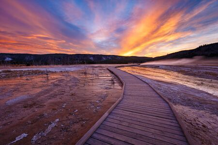 Sapphire Pool with blue steamy water and beautiful colorful sunset. Yellowstone, Wyoming, USA Foto de archivo