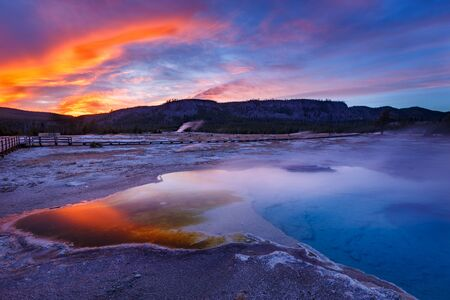 Sapphire Pool in Biscuit basin with blue steamy water and beautiful colorful sunset. Yellowstone, Wyoming, USA