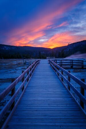 Biscuit basin walkway with blue steamy water and beautiful colorful sunset. Yellowstone, Wyoming, USA Foto de archivo