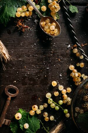 Top view of an empty copy space surrounded by white currant berries on a dark wooden table