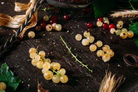 Bunch of white currant disassembled with mix of red and white currant around, laying on a dark wooden table