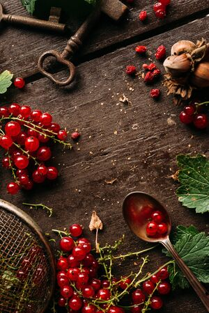 Table top view on a bunch of redcurrant on a dark wooden table with empty blank copy space for a text Standard-Bild